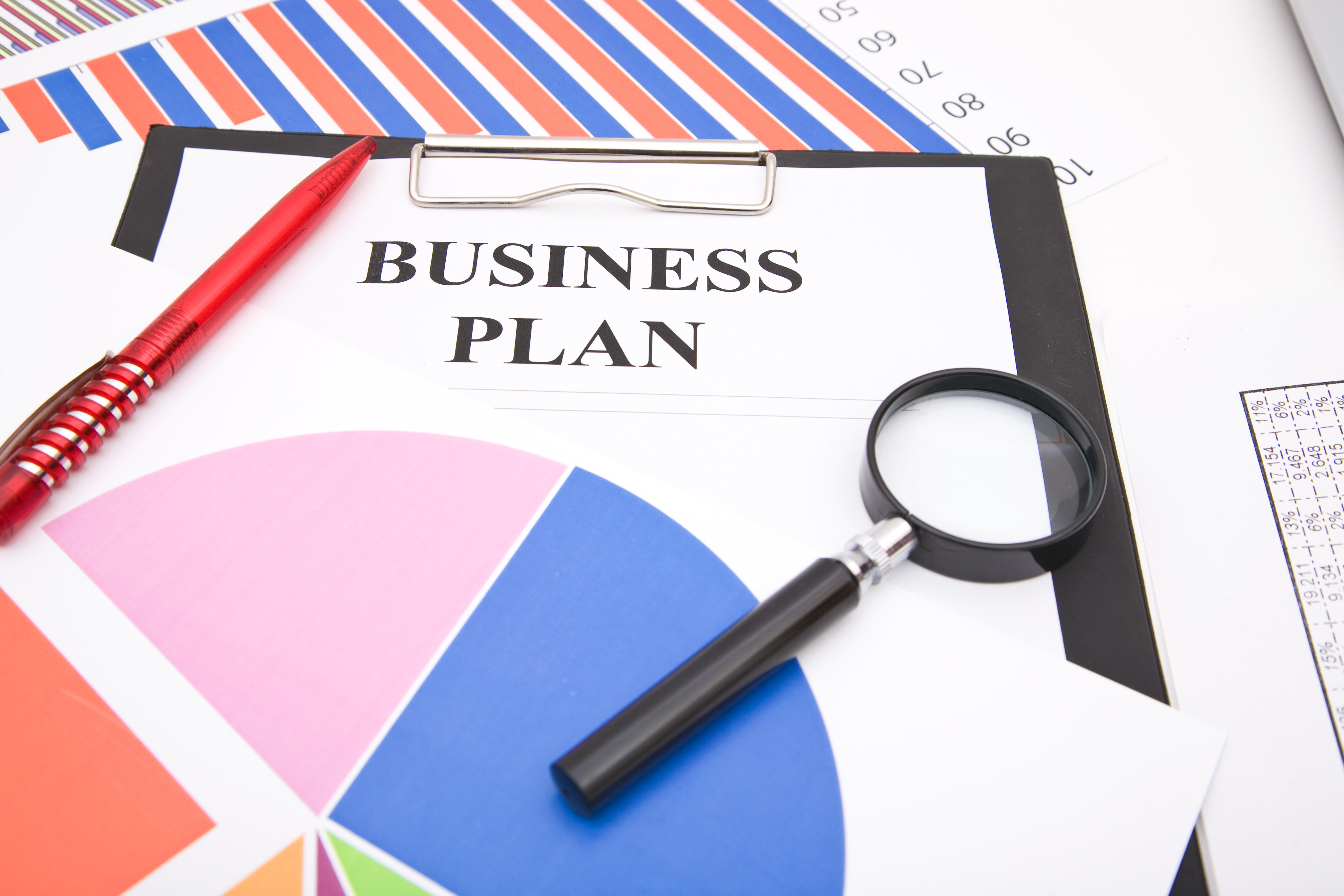 business concept of an office desk with charts business plan form pen