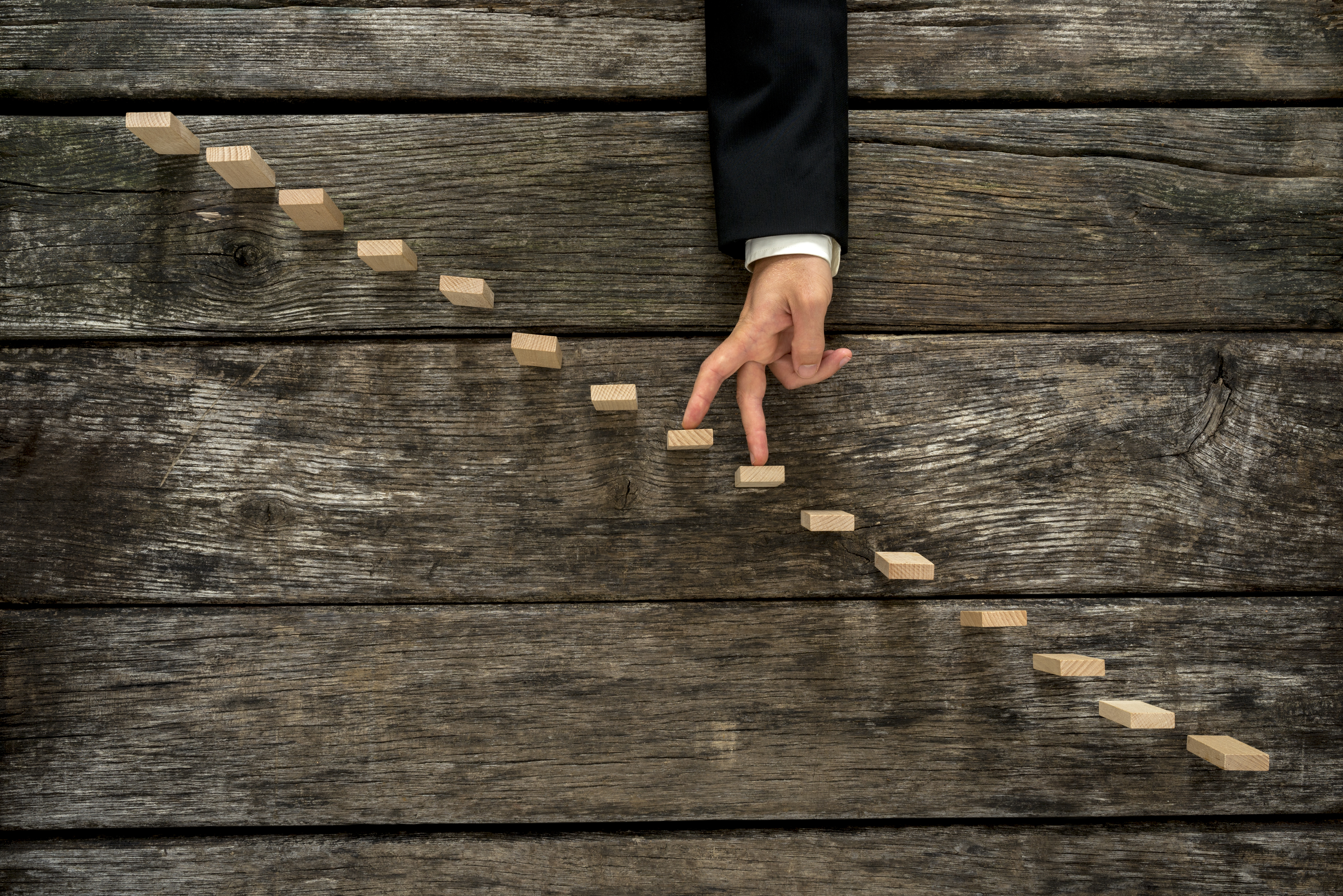 Businessman walking his fingers up wooden steps or pegs resembling a staircase mounted in rustic wooden boards in a conceptual image of success promotion and advancement.