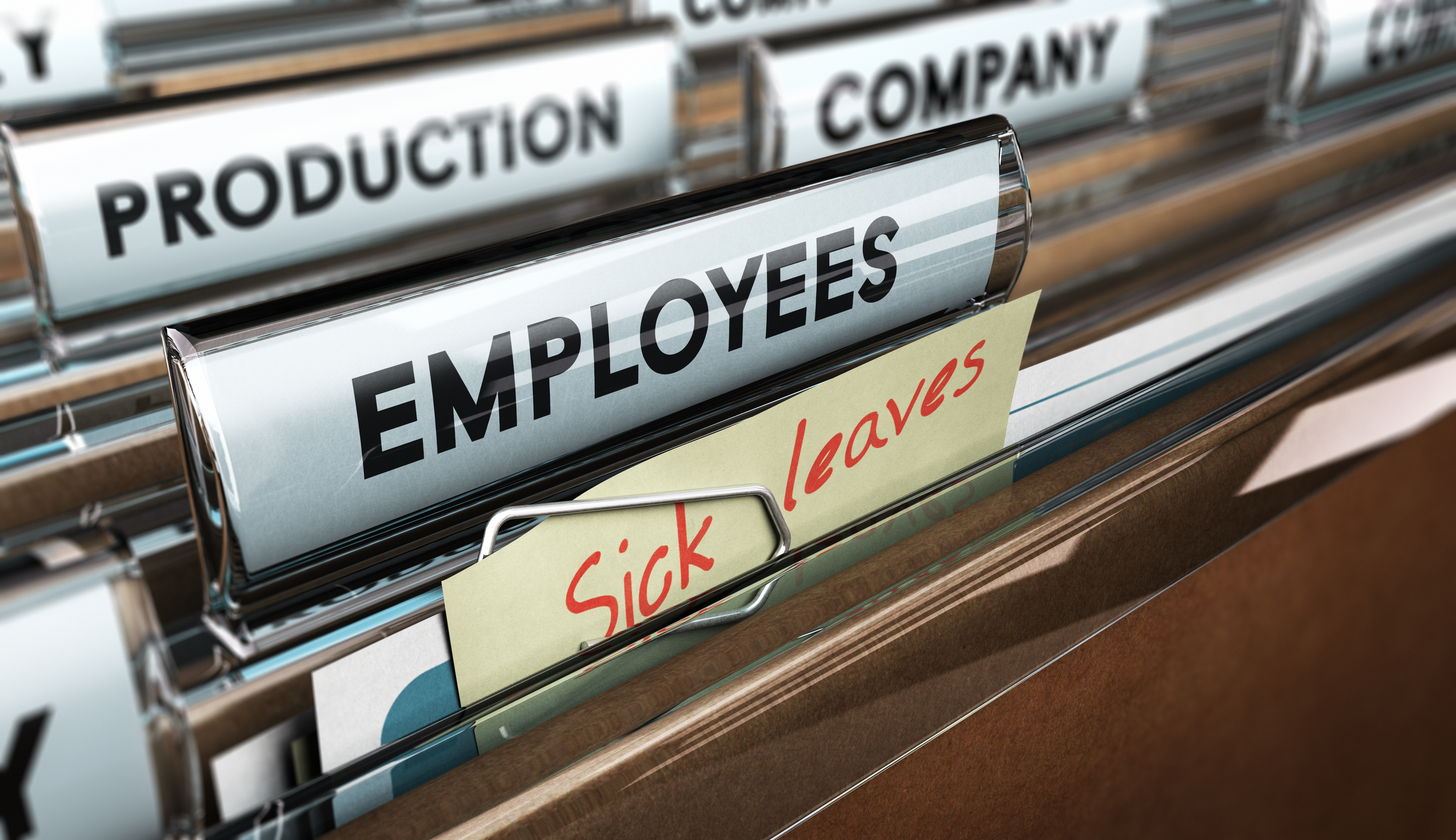 Close up on a file tab with the word employees plus a note with the text sick leaves blur effect at the background. Concept image for illustration of sick leave entilement.