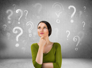 Beautiful woman with questioning expression and question marks above her head